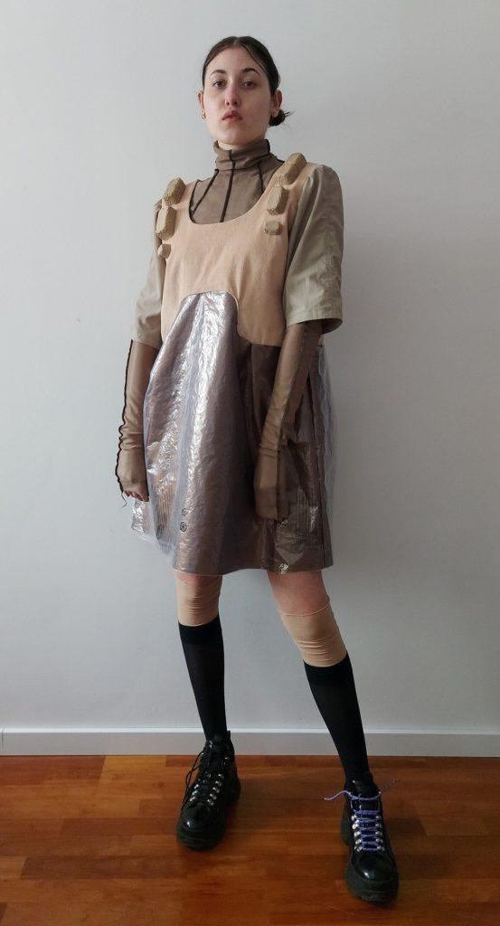 Zdjęcie przedstawia postać na tle białej ściany. Modelka jest ubrana w golf i trzykolorową sukienkę, Spodnia część stroju to bluzka z golfem i bardzo długimi rękawami przykrywającymi dłonie. Od linii wszycia golfu rozchodzą się promieniście ozdobne czarne przeszycia. Sukienka z dużym owalnym dekoltem i rękawem ¾. Karczek sukienki o fantazyjnym kształcie został wykonany ze sztruksu w kolorze pudrowego różu. Dół sukienki dwuwarstwowy, lekko rozszerzany Wierzchnia warstwa dołu sukienki uszyta z folii opakowaniowej. Rękaw ¾ z zakładkami ułożonymi na główce rękawa z zielonoszarej bawełny. Całości dopełniają czarne podkolanówki i czarne sznurowane półbuty.