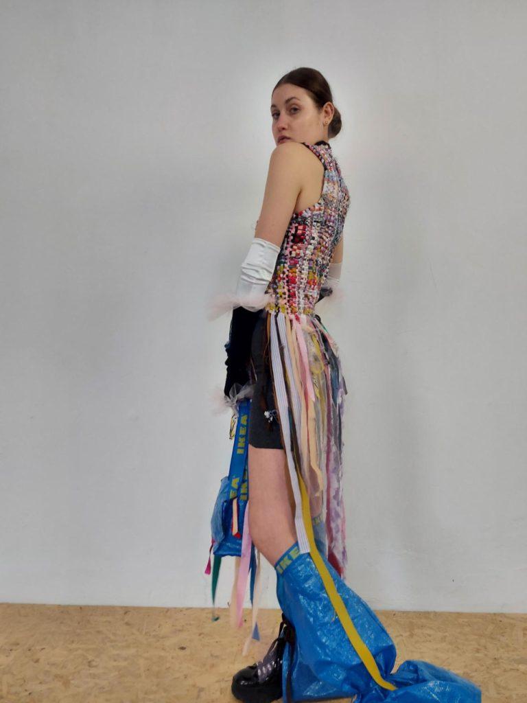 Wielokolorowy golf stworzony ze ścinków materiałów zebranych od znajomych. Patchwork z dżinsu kupionego w second handach ozdabia górną część sukienki wykończoną czarnymi falbankami, dół stworzony jest z plastikowej folii opakowaniowej uratowaną przed śmietnikiem. Pod sukienką widoczne sportowe dzianinowe spodenki. Dodatki wykonane z kultowych niebieskich toreb ze sklepu ikea.